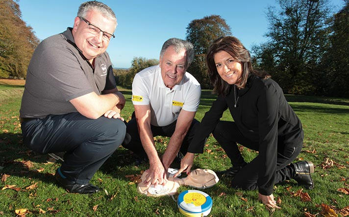 Paul Williams, Bernard Gallacher and Trudie Lobban MBE on a golf course with a defibrillator